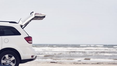 Car with open trunk on beach by sea